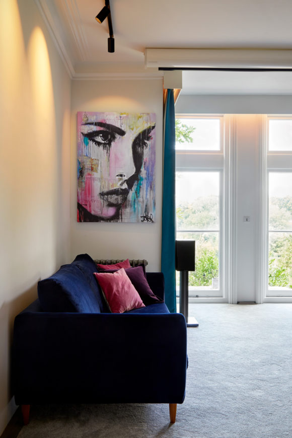 sitting room, artwork, track lighting, blue velvet sofa