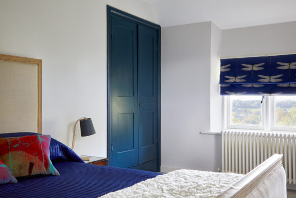 guest bedroom with blue wardrobe, patterned roman blind