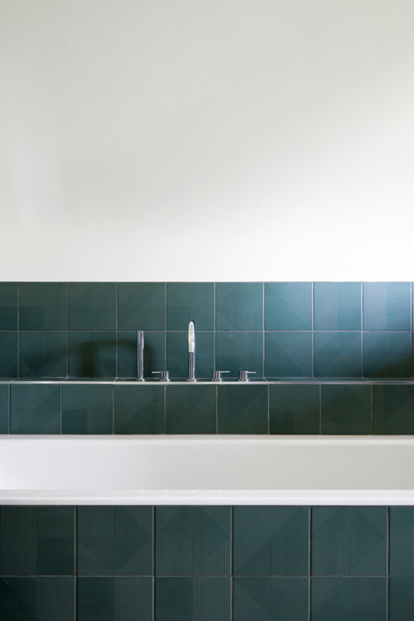 en-suite bathroom with green tiles